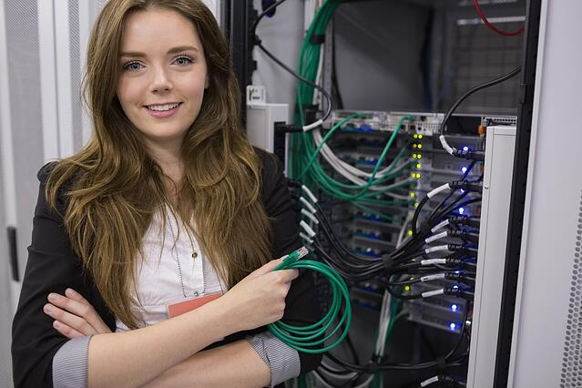 Girl holding cable in front of rack mounted servers in data storage facility.jpeg