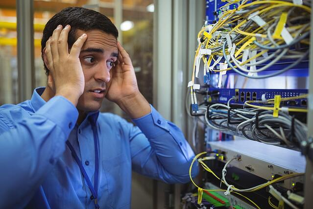 Technician getting stressed over server maintenance in server room-1.jpeg